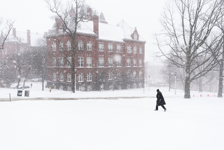 Person trudges across Bascom Hill near Science Hall in snowstorm.