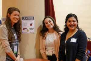 Intern volunteers Anna Weinberg, Ally Burg, and Noemy Serrano (L-R) pose near a zero waste station in the exhibitor hall at Monona Terrace. The team helped the Nelson Institute Earth Day Conference achieve zero waste status in 2018.
