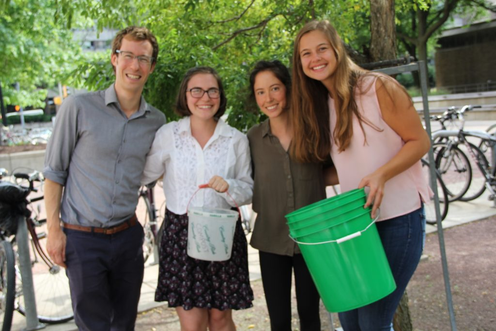 Green Fund Program Manager Ian Aley, and students Jackie Millonzi, Lauren Lucas, and Katie Piel stand with one of the new green compost buckets purchased through the Green Fund.