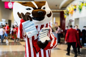 """UW-Madison mascot Bucky Badger helps volunteers distribute complimentary copies of """"The Death and Life of the Great Lakes"""" following the Chancellor's Convocation for New Students at the Kohl Center at the University of Wisconsin-Madison on Sept. 4, 2018. (Photo by Jeff Miller / UW-Madison)"""