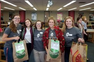 Office of Sustainability interns holding compost bags at the College Library #StudyStrong Academic Resource Fair, where signage for #RecycleRight was initially piloted. Photo by Nathan Jandl.