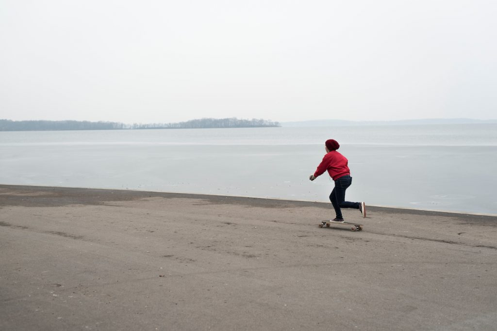 While many Badgers have left campus for winter break, a lone woman rolls her longboard along the Memorial Union Terrace at the University of Wisconsin-Madison past a partially frozen Lake Mendota on Dec. 21, 2014. In the background is Picnic Point. (Photo by Jeff Miller/UW-Madison)