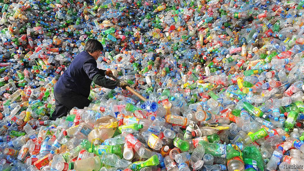 A worker in a pile of plastic bottles. Image courtesy the The Economist.