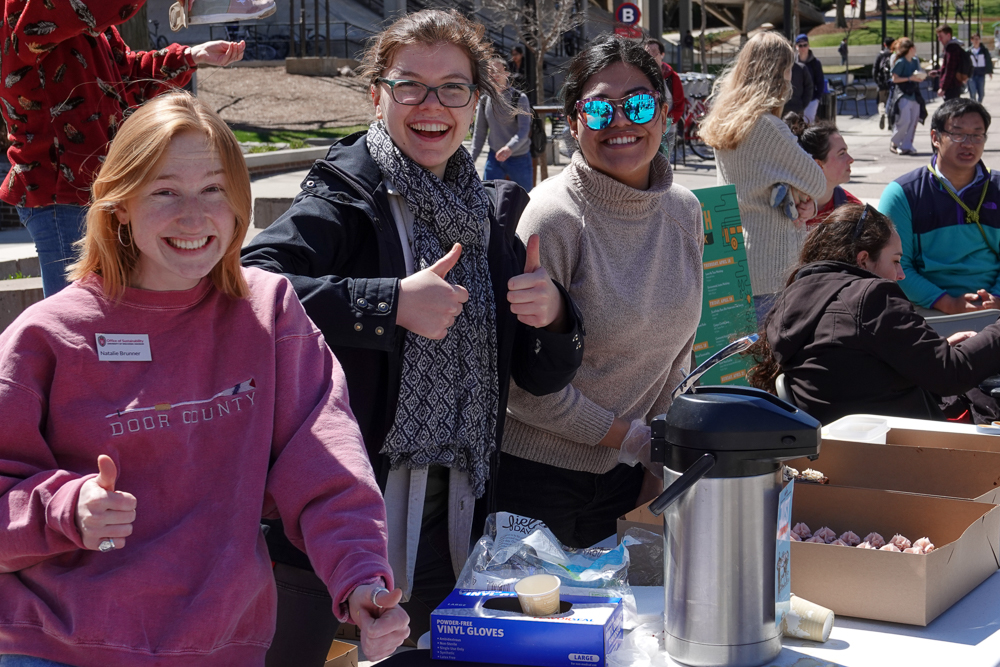 Office of Sustainability interns Natalie Brunner, Hannah Kasun, and Noemy Serrano (L-R) having fun and serving treats from Bloom Bake Shop during Fix-It Friday. Photo by Nathan Jandl.