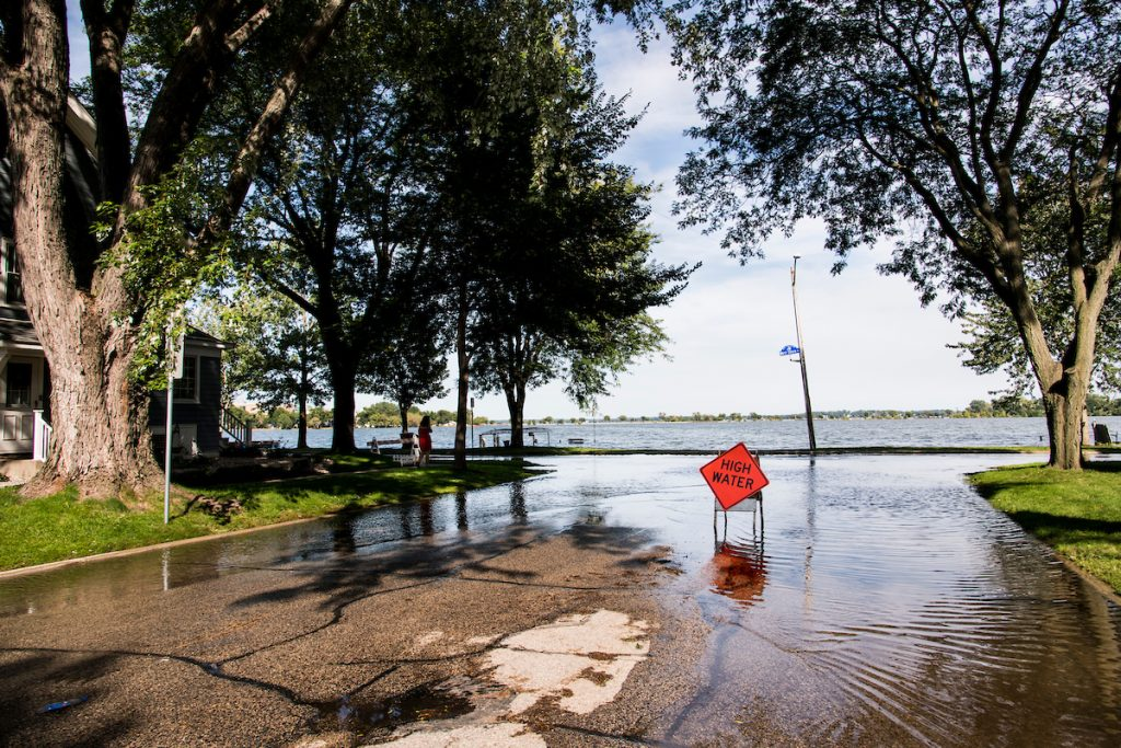 A road hazard sign warns of high-standing water flooding West Shore Drive along Monona Bay in Madison, Wis., during summer on Sept. 6, 2018. Area lake levels continue to rise after a record-breaking storm on Aug. 20 dumped more than 10-inches of rain on parts of Dane County, also flooding areas of the University of Wisconsin-Madison campus lakeshore. (Photo by Jeff Miller / UW-Madison).